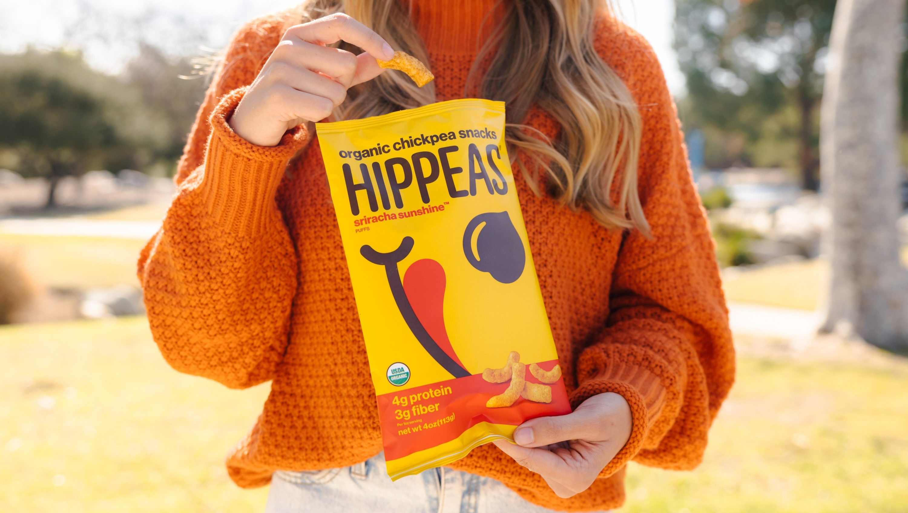 A female holding a bag of Hippeas