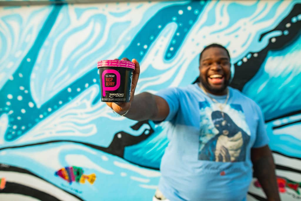 Man holding pint of raspberry sweetpea non-dairy ice cream in front of ocean mural.