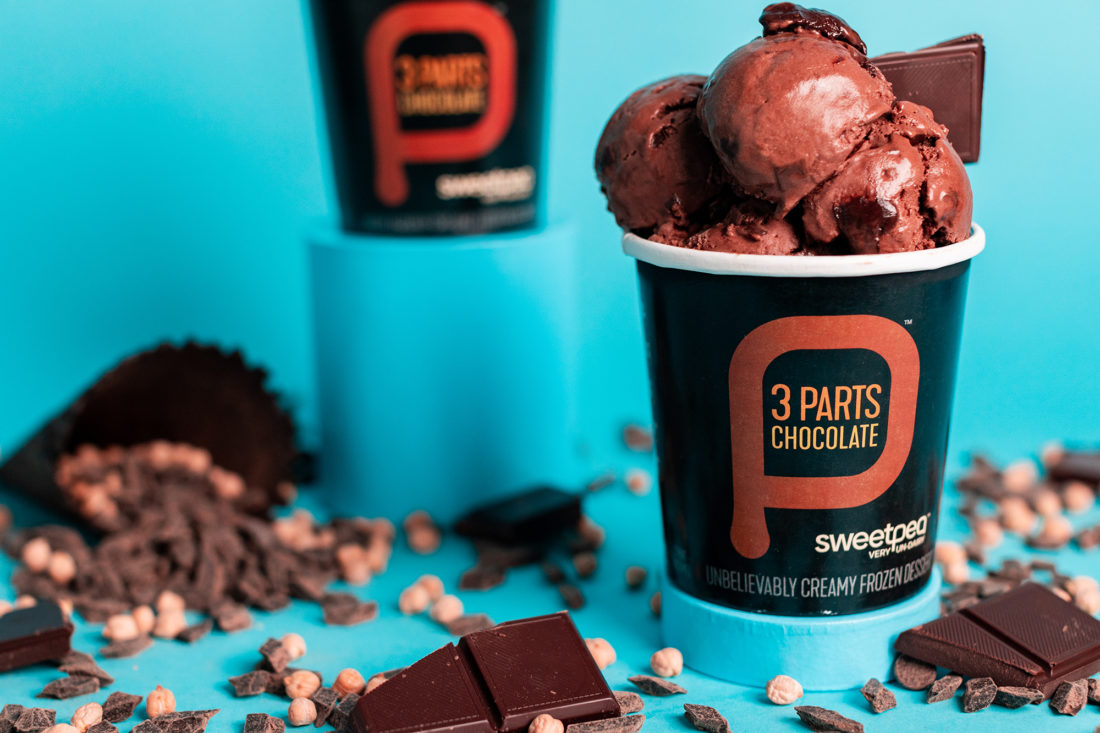 Two pints of SweetPea plant-based chickpea ice cream flavor 3 Parts Chocolate against a teal blue background