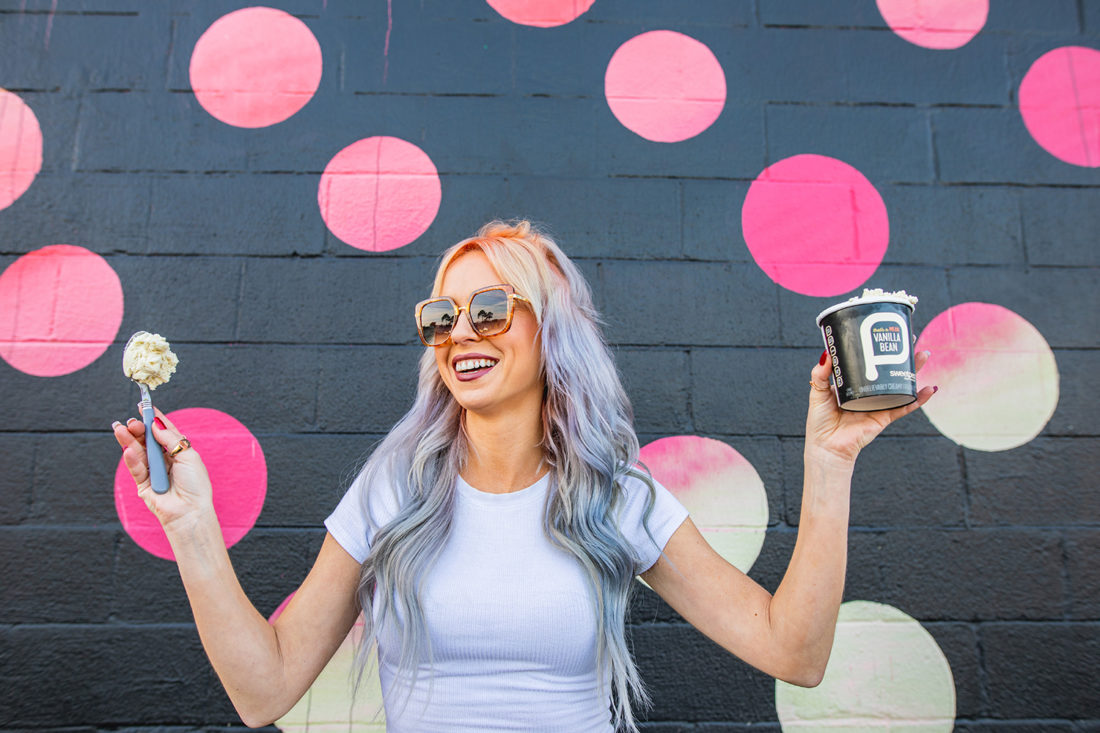 Edgy woman standing in front of a black and pink mural holding a pint of sweetpea plant-based ice cream.