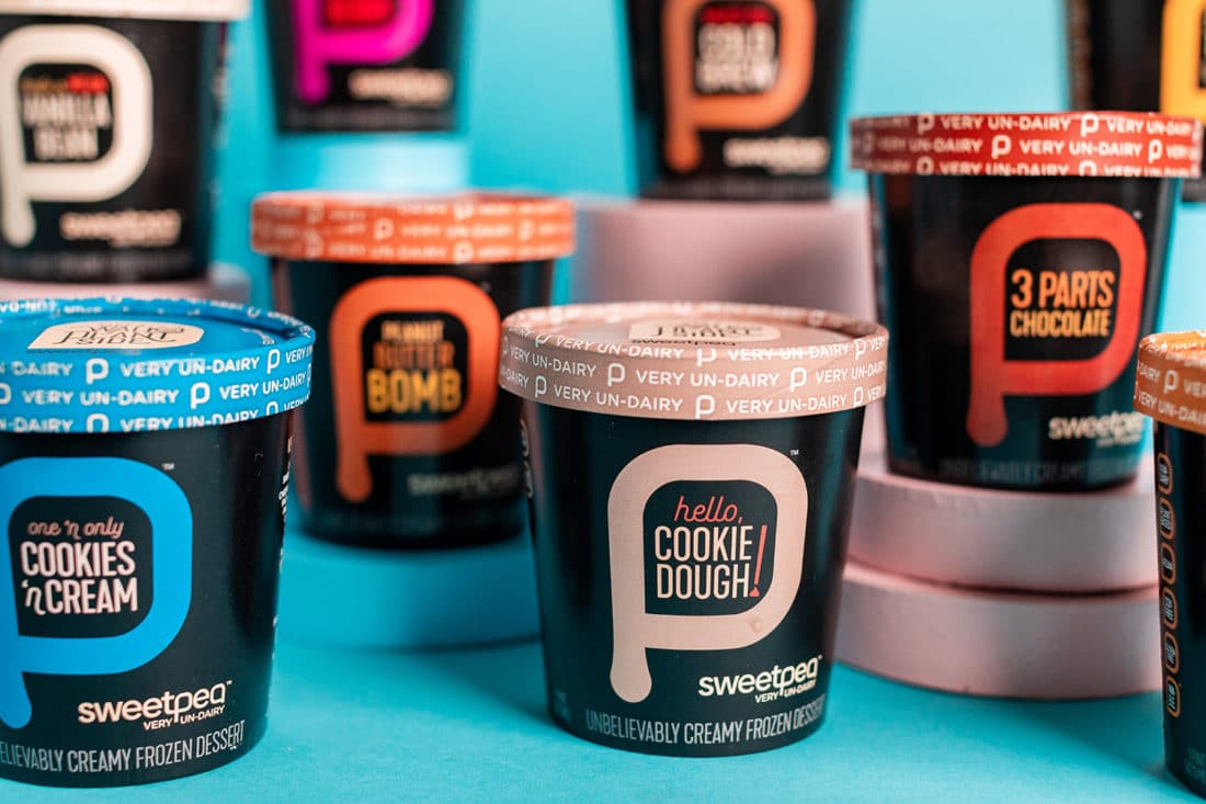 Multiple, colorful pints of SweetPea non-dairy ice cream displayed against a teal background